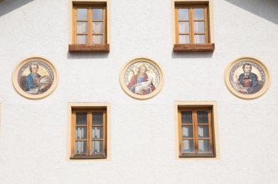 Fassade Peter-Anich-Haus mit Porträts von Peter Anich, Blasius Hueber und Christus