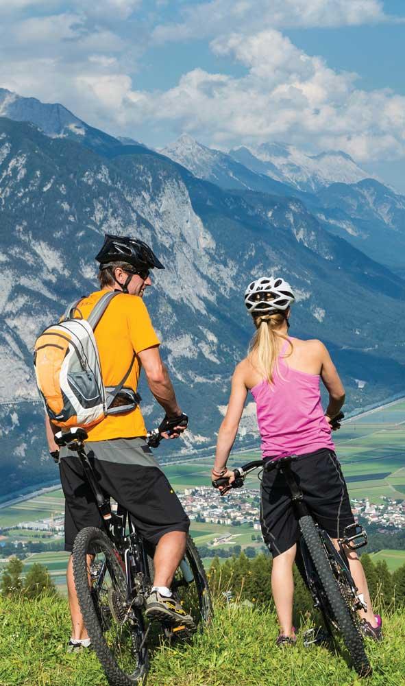 Zwei Mountainbiker genießen das Panorama von Stieglreith in Richtung Innsbruck