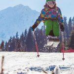 Junges Mädchen mit Skiern springt gekonnt über eine kleine Schanze