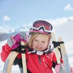 Ein kleines Mädchen mit Skihelm posiert mit ihrer Rodel für die Kamera