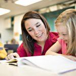 Eine Lehrerin erklärt einem Mädchen die nächste Aufgabe